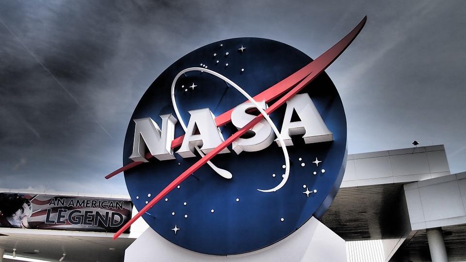 le logo de la NASA devant un ciel agité